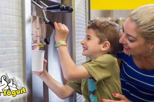 mom and son pouring frozen yogurt at yukon yogurt